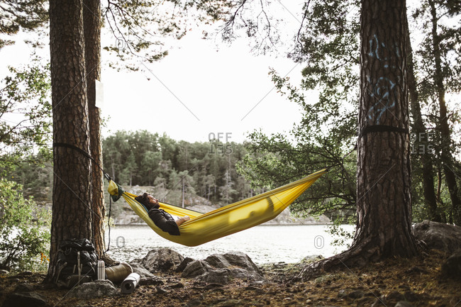 Young man with book sleeping in hammock in forest