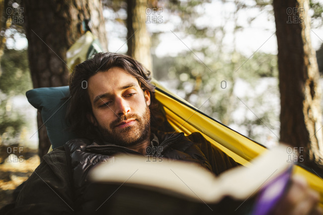 Young man reading book while lying on hammock in forest