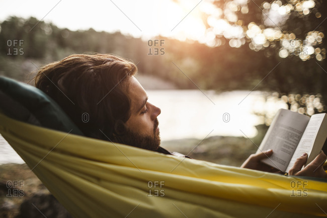 Contemplating man reading book while lying over hammock in forest