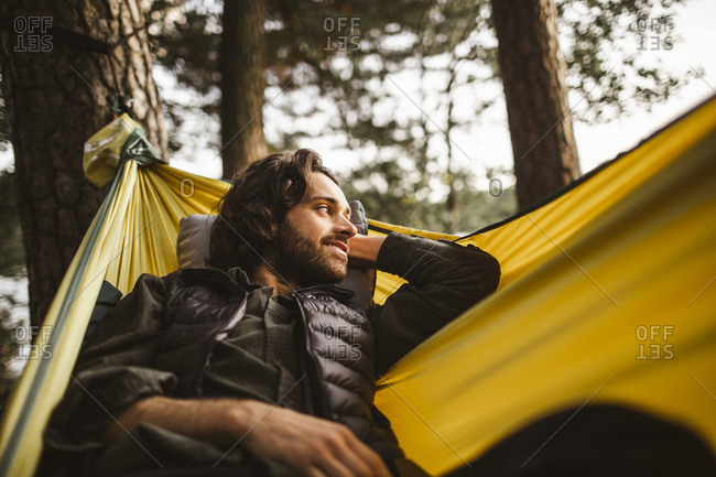 Smiling man looking away while lying over hammock in forest