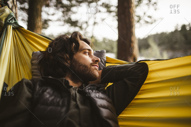 Contemplating man looking away while lying over hammock in forest