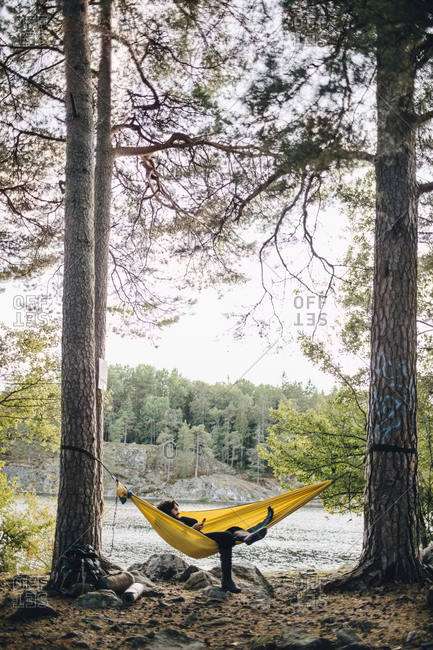 Contemplating man using smart phone while lying over hammock in forest