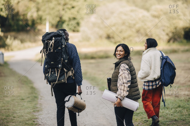 Portrait of smiling female with friends walking on footpath