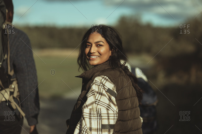 Portrait of smiling woman with friends walking on footpath