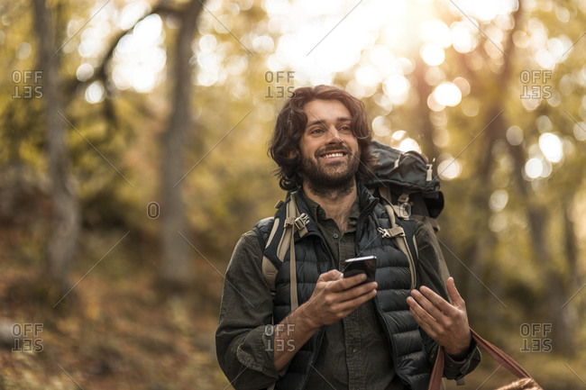 Smiling man using smart phone while looking away in forest