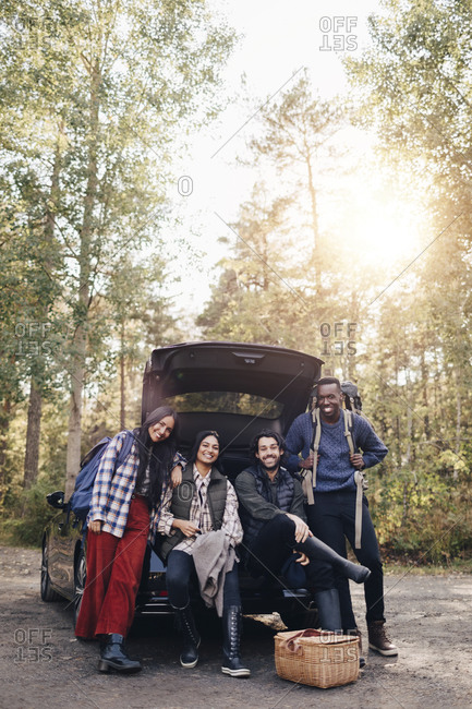 Portrait of smiling male and female friends by car trunk during vacation
