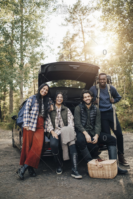 Portrait of smiling male and female friends sitting in car trunk during vacation
