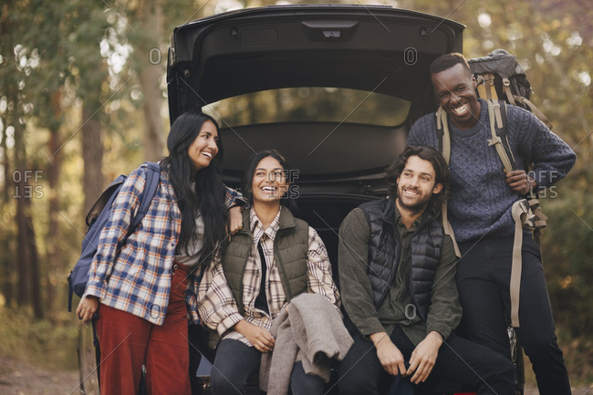 Smiling male and female friends sitting in car trunk during vacation
