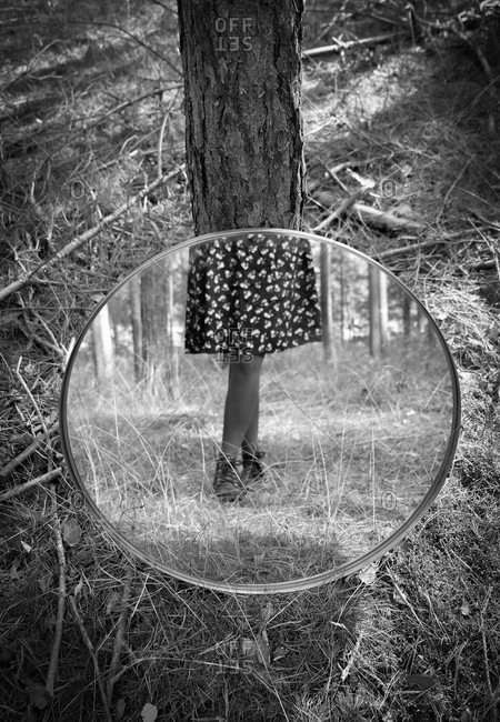 Mirror resting on a tree with a female wearing a skirt reflecting in black and white