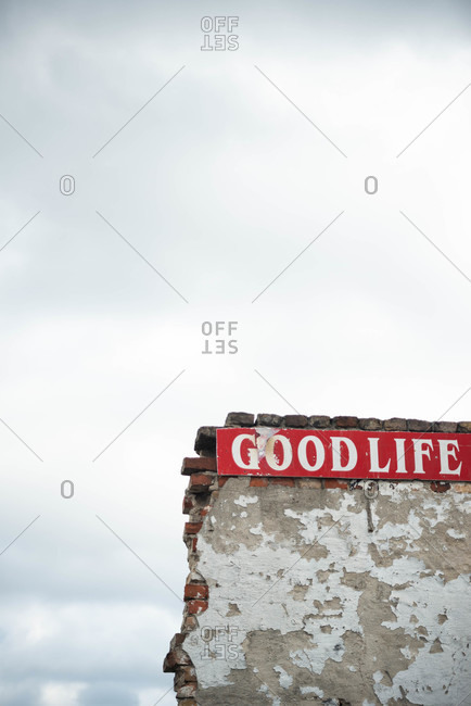 Old crumbling wall with Good Life sign under cloudy sky