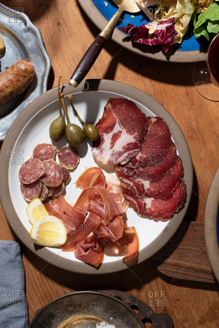 Sliced meats on a plate with capers