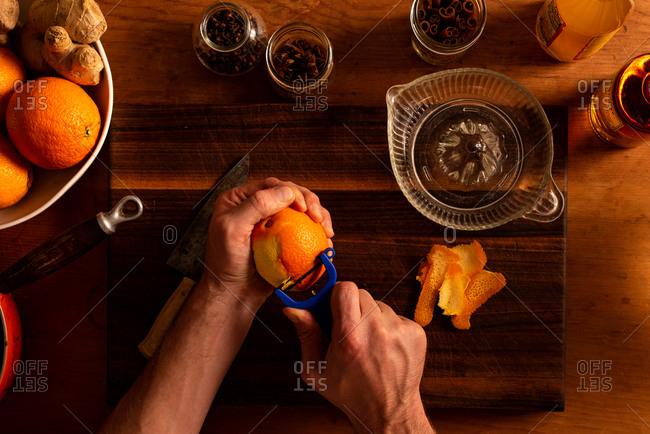 Peeling an orange for a mulled apple cider and orange cocktail