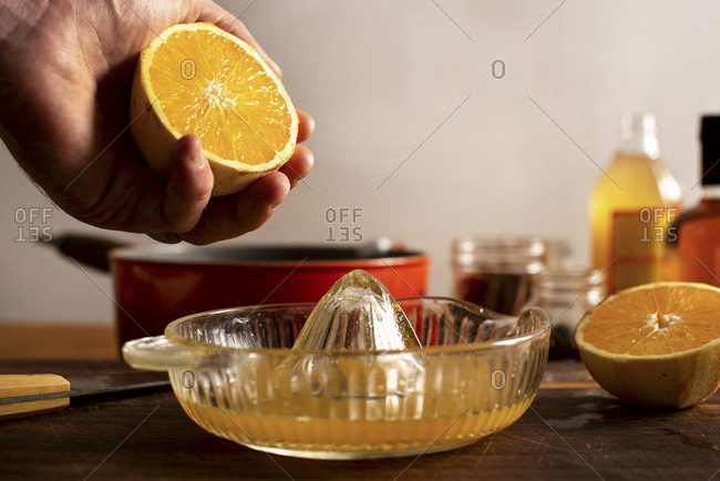 Juicing an orange for a mulled apple cider and orange cocktail