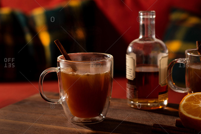 Mulled apple cider and orange cocktails on wooden table beside bottle of liquor
