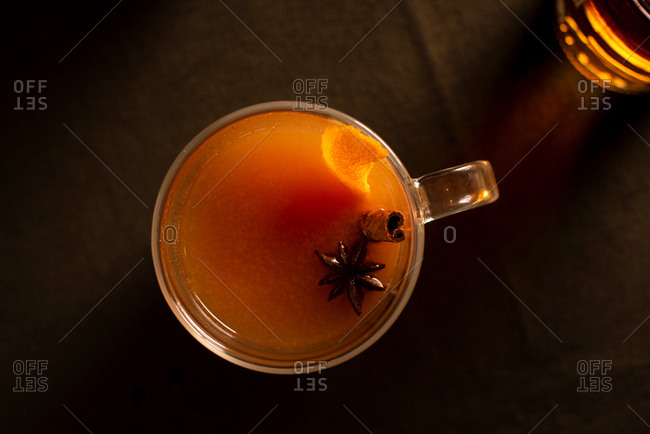 A top down of a mulled apple cider and orange cocktail