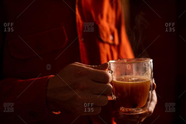 Man holding a mug of steaming mulled apple cider and orange cocktail