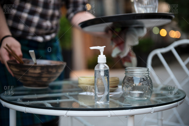 Hand sanitizer sits on a table at restaurant outdoors