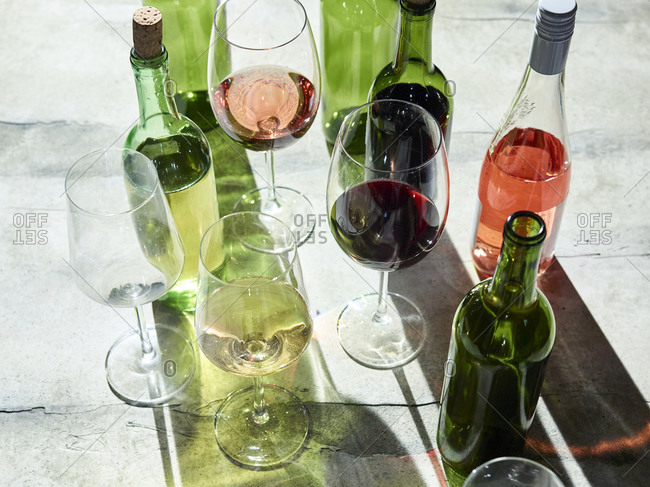 Samples of different flavored wines in glasses beside bottles
