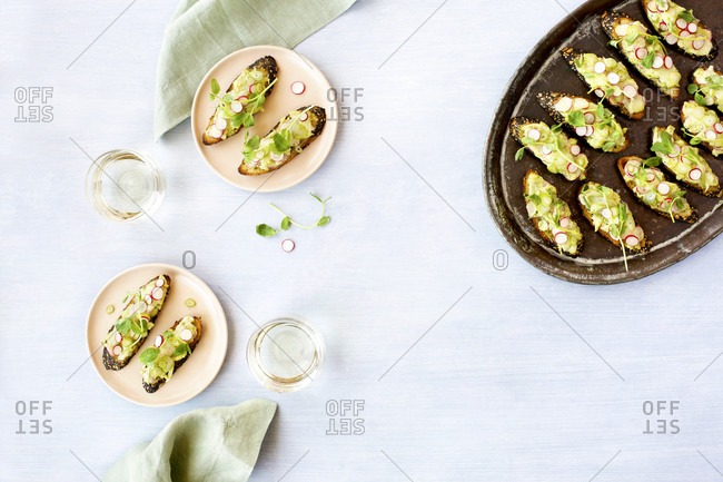 Radish fennel manchego crostini with fresh pea pesto on a tray and plates