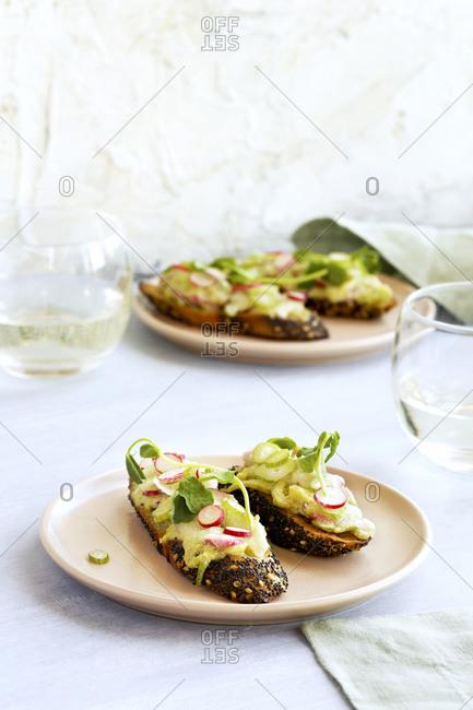 Radish fennel manchego crostini with fresh pea pesto served on plates on white surface