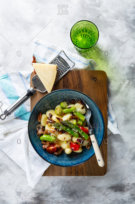 Overhead view of gnocchi in a blue bowl on light table