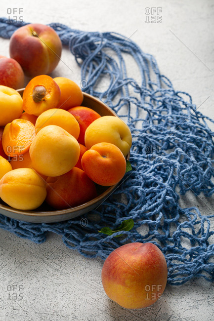 Ripe organic nectarines and peaches with blue net bag