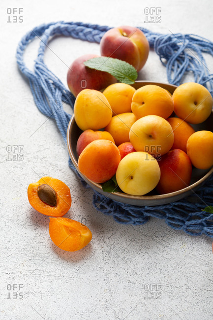 Bowl full of apricots and peaches on light surface beside net bag
