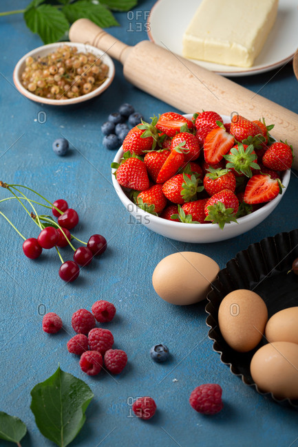 Fresh berries and other summer pie ingredients on table