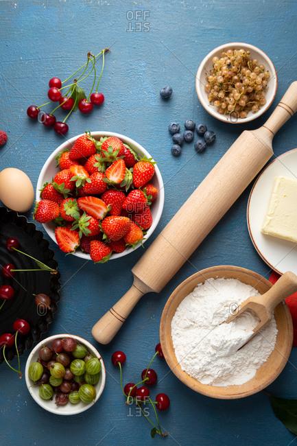 Overhead view of summer berries tart ingredients on blue background