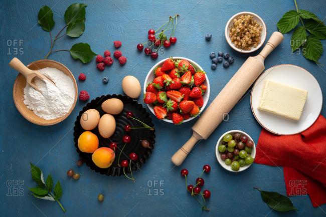 Summer berries tart ingredients on blue background