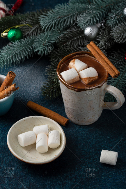 Cups of hot chocolate with cinnamon sticks and marshmallows on a dark blue background