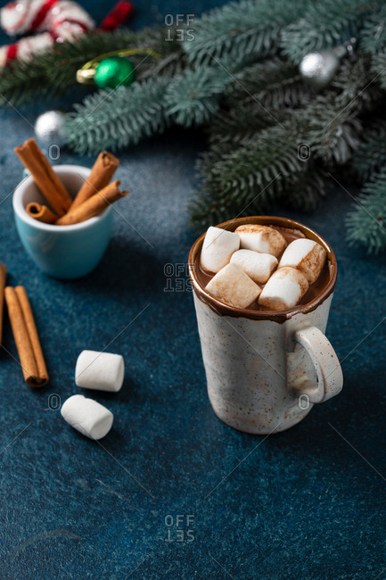 Mug with hot chocolate with cinnamon sticks and marshmallows on a dark blue background