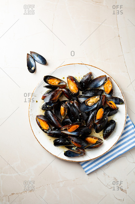 Overhead view of mussels with sauce on light surface