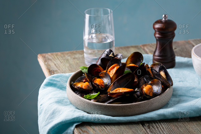 Mussels with sauce in bowl on wooden table