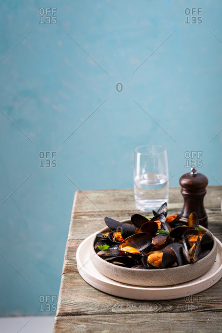 Seafood with sauce in bowl on wooden table