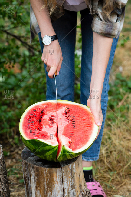 Woman cutting a watermelon outdoors
