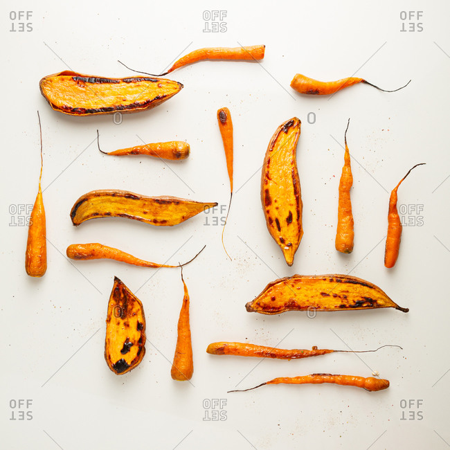 Overhead view of roasted root vegetables arranged on light surface