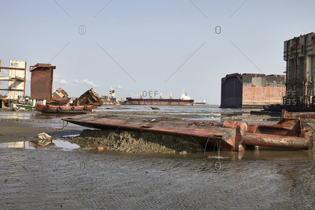 Old ships and parts scattered in the mud at the Chittagong Ship Breaking Yards in Chittagong, Bangladesh