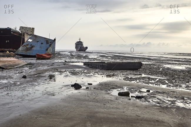 Large ships and ship parts scattered in the mud at the Chittagong Ship Breaking Yards in Chittagong, Bangladesh