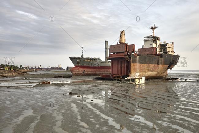 Chittagong, Bangladesh - May 11, 2013: Workers doing risky and hard work on partially disintegrated ships at Chittagong Ship Breaking Yards