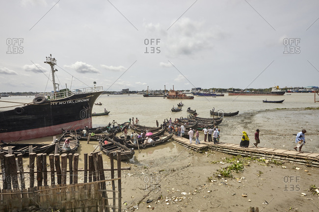 Chittagong, Bangladesh - May 11, 2013: Passengers boarding boats at Karnaphuli River with large commercial ships on anchorage visible in the back