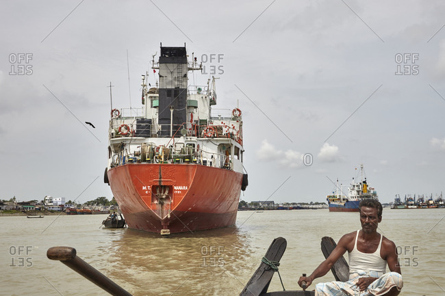 Chittagong, Bangladesh - May 11, 2013: Bangladeshi boatman rowing his boat in front of old big ships near the Sadarghat River port on the Karnaphuli River