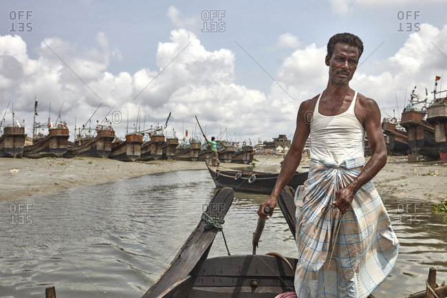 Chittagong, Bangladesh - May 11, 2013: Man wearing traditional clothing rowing a boat in front of Ancient looking and abandoned ships anchored on the River Karnaphuli