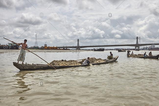 Chittagong, Bangladesh - May 11, 2013: Bangladeshi boatman navigating a heavily loaded boat in front of the Shah Amanat Bridge on the Karnaphuli River