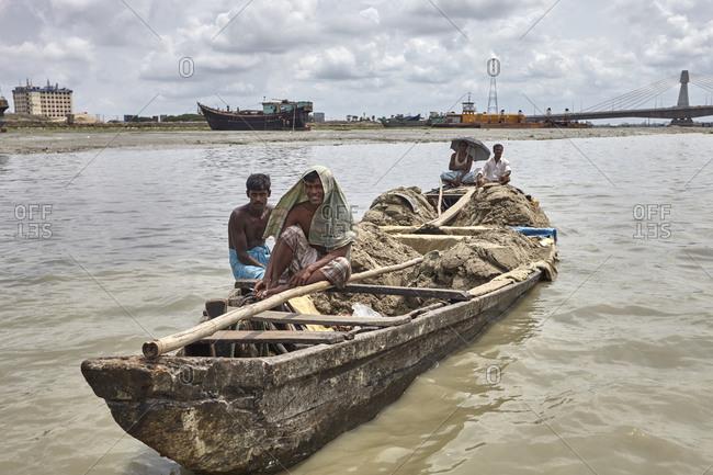 Chittagong, Bangladesh - May 11, 2013: Local workers navigating a heavily loaded boat in front of the Shah Amanat Bridge on the Karnaphuli River
