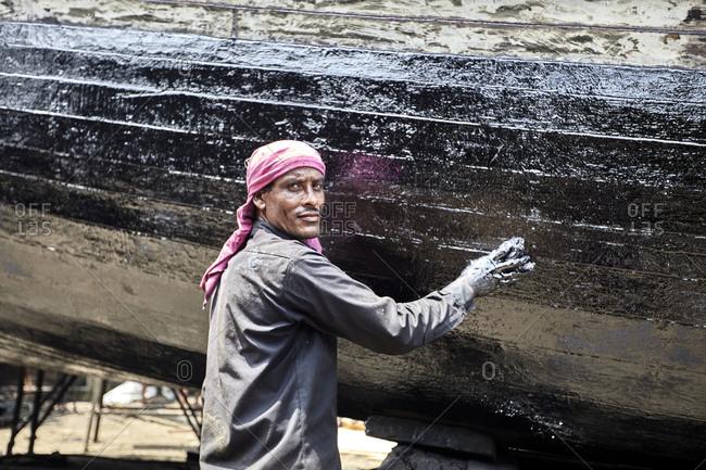 Chittagong, Bangladesh - May 11, 2013: A man working on a traditional fishing boat at a shipyard by the Karnaphuli River