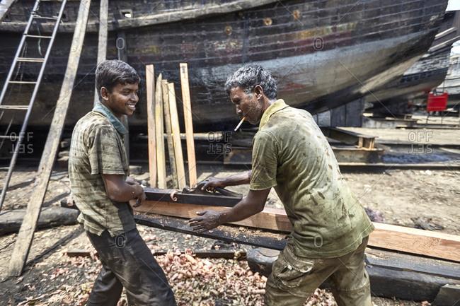 Chittagong, Bangladesh - May 11, 2013: Two men working on a traditional fishing boat at a shipyard by the Karnaphuli River