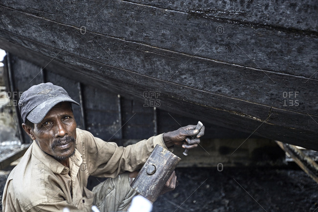 Chittagong, Bangladesh - May 11, 2013: Portrait of a shipbuilder with hammer and nail in front of a traditional fishing boat at a shipyard by the Karnaphuli River