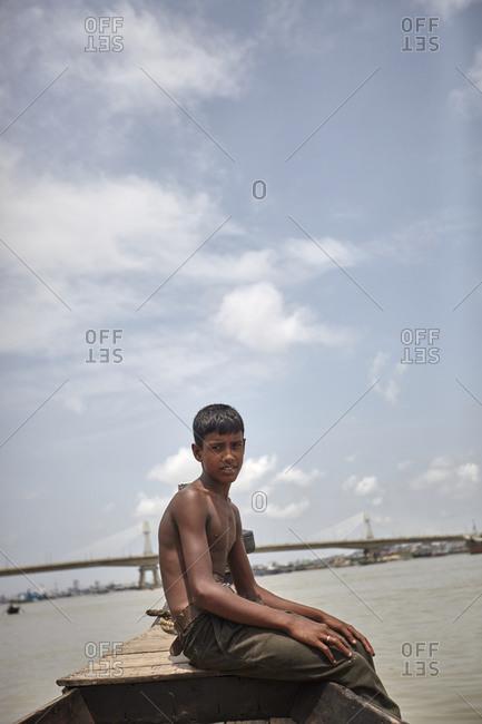 Chittagong, Bangladesh - May 11, 2013: A boy siting on a boat on the Karnaphuli River