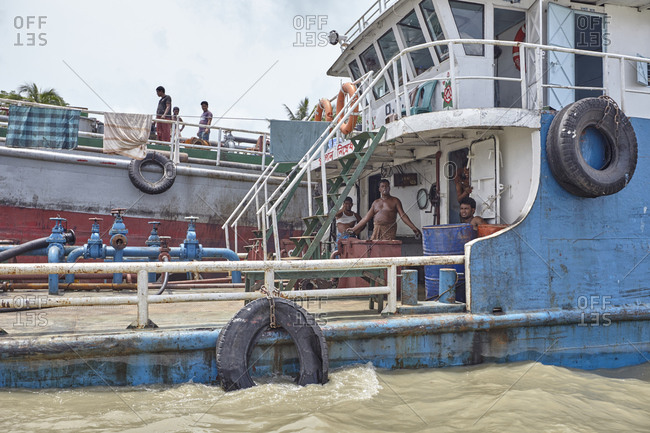 Chittagong, Bangladesh - May 11, 2013: Ship crew members doing maintenance work on their ship while lying at anchor on the Karnaphuli River not far from the Bay of Bengal